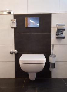 Abbildung zeigt die Montagehöhe Toilettenpapierhalter neben einem weißen breiten WC mit verschiedenen Armaturen wie Klobürsten Halter und Klopapier Halter